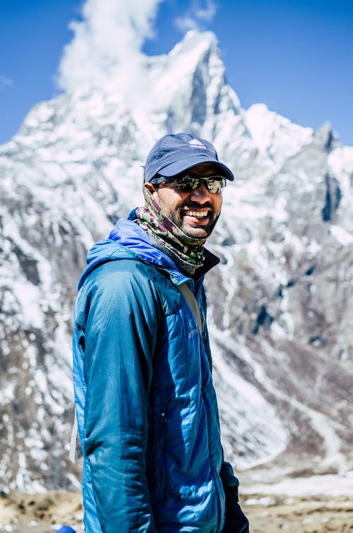 Happy young ethnic man smiling while standing near snowy mountains on sunny day