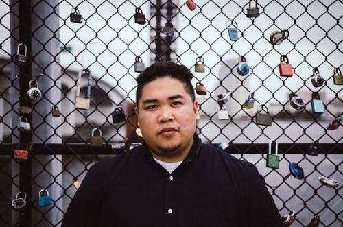 Calm young overweight Asian male with dark hair in casual clothes standing near chain link fence with colorful locks and looking at camera at riverside