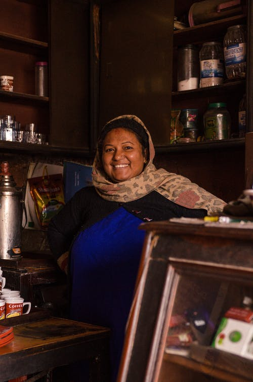 Cheerful Muslim woman standing in traditional shop and smiling