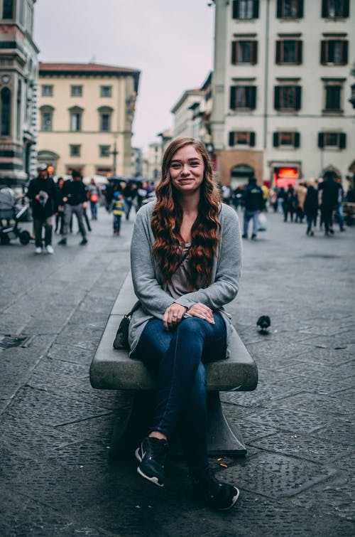 Positive young female traveler recreating on city square during sightseeing trip