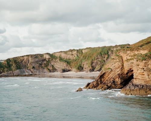 Amazing scenery of rough rocky cliffs surrounding sandy beach washing by foamy ocean under cloudy sky