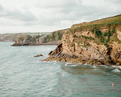 Picturesque seascape with rough rocky cliffs covered with green grass against dramatic cloudy sky