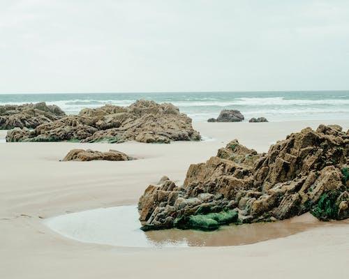 Spectacular scenery of rough rocky formations on sandy beach near powerful wavy ocean against overcast sky