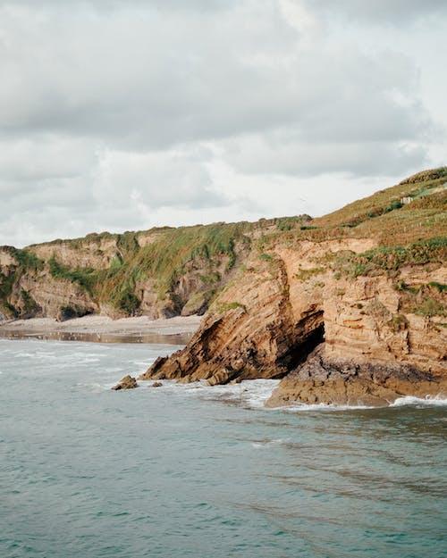 Powerful ocean washing rocky cliffs and sandy beach under cloudy sky