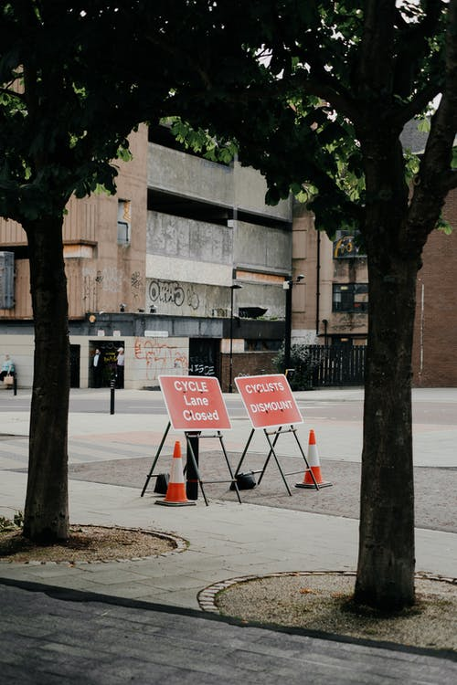 Temporary road signs with Cycle Lane Closed inscription placed on pavement near sidewalk and building on city street