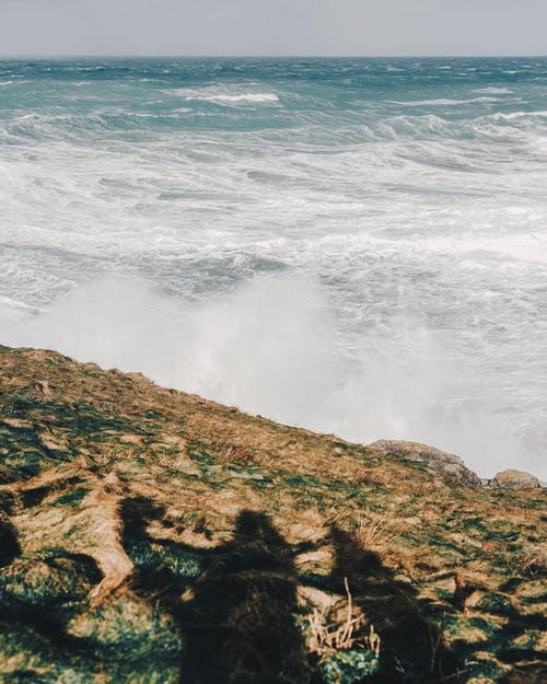 Endless stormy sea crashing over rocky cliff