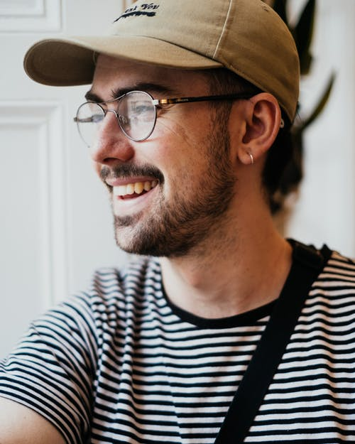 Happy unshaven young guy in casual cap and eyeglasses smiling and looking away in light room
