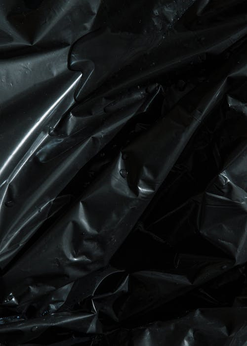 From above of smooth surface of black crumpled plastic bag as abstract background