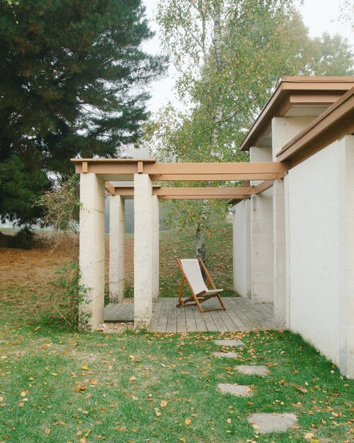 Exterior of concrete house with wooden details and pillars near green lawn with stone steps
