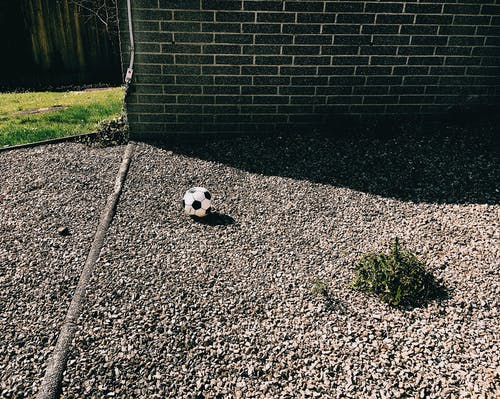 Pebble ground with ball near building and grass