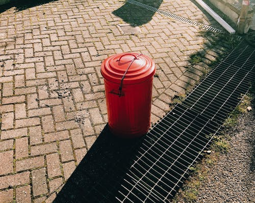 High angle of red metal trash can placed on pavement near sewer grates in city street in sunny summer day