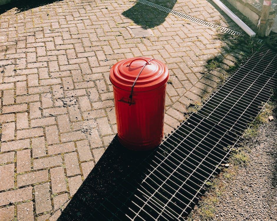 Cubo De Plástico Rojo Sobre Piso De Ladrillo