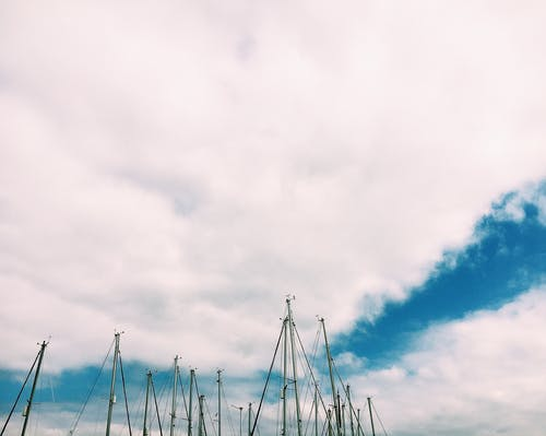 Sailboats with deflated sails under cloudy sky