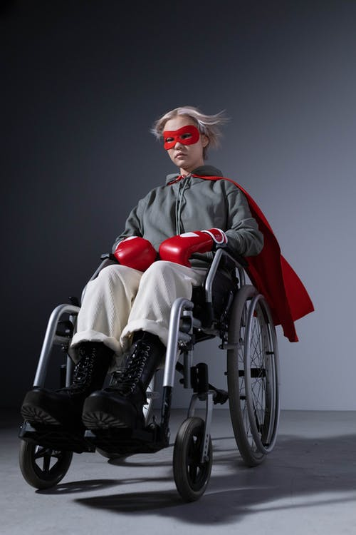 Woman in Black and White Jacket Sitting on Black Wheelchair
