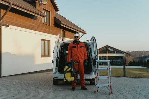 Man in Working Clothes With A Vaccum Cleaner Standing Beside A Service Van and Stepladder