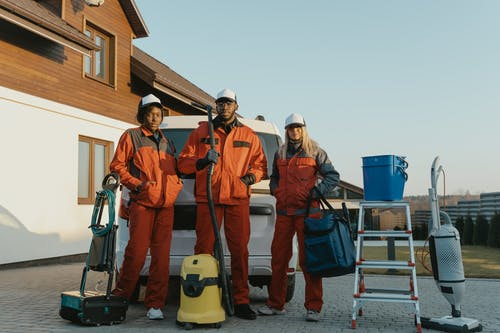 3 Men in Orange Jacket and Helmet Standing Beside White and Yellow Water Jug