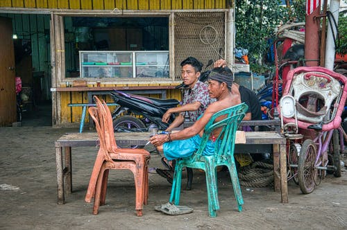 Ethnic males smoking cigarettes sitting near wooden bench and hut in poor Asian town