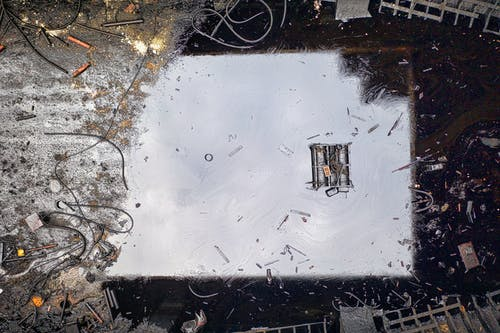 Top view of black reflecting dirty river contaminated with oil products and litter