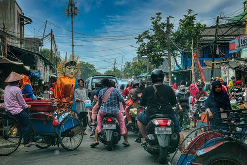 Ethnic people walking of crowded street near road with cars and motorcycles in Asian town