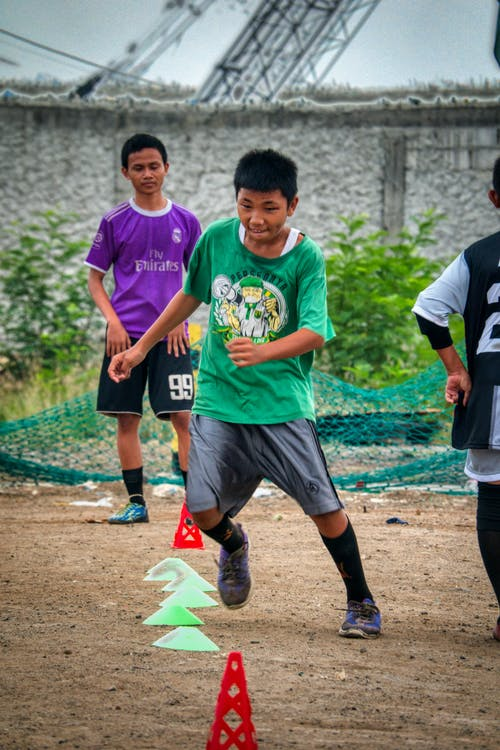 Active ethnic teen player running fast through training cones while practicing speed with boys