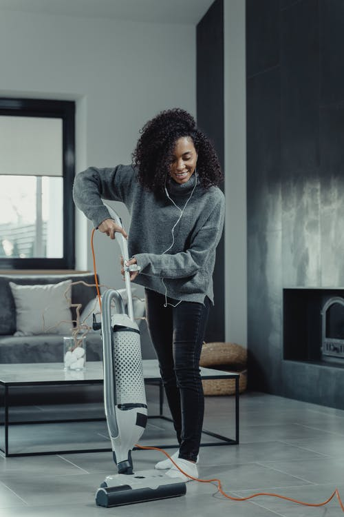 Woman in Gray Sweater and Blue Denim Jeans Standing Beside Black and White Luggage Bag