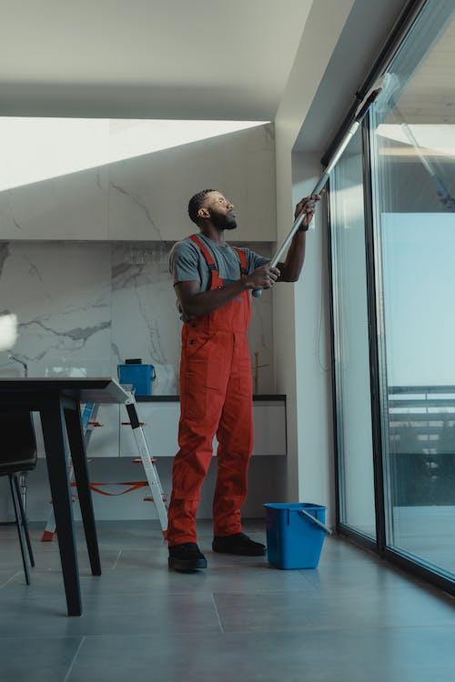 Man in Orange Pants Standing Near Glass Door