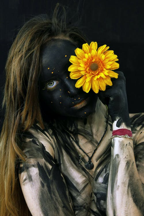 Woman in Black Leather Jacket With Yellow Sunflower on Her Face