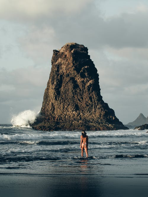 Woman in swimsuit standing in wavy sea with rocky cliff