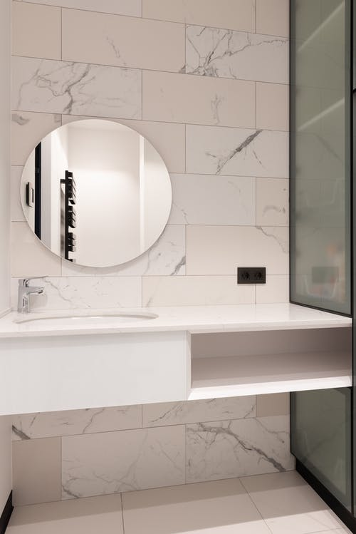 Interior of modern bathroom with marble tiled walls and round mirror over sink