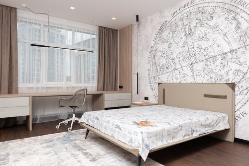 Modern room with wide bed under map on wall and long table with comfortable chair
