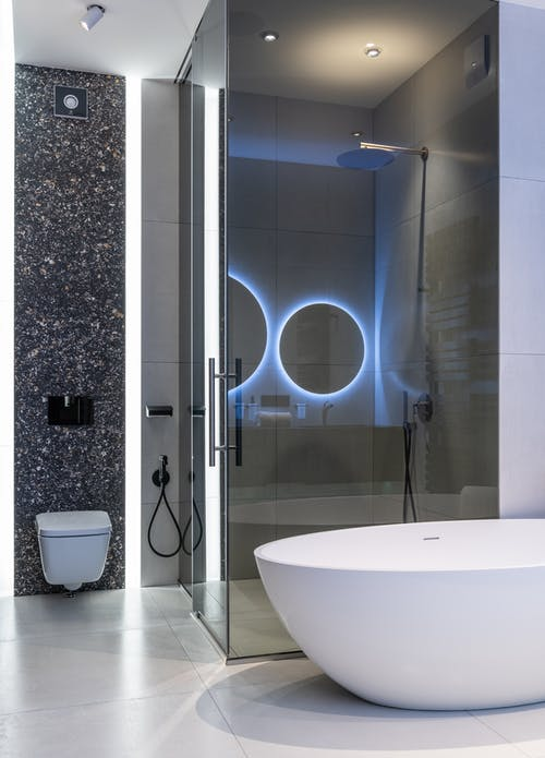 Interior of modern spacious bathroom with bright lamps