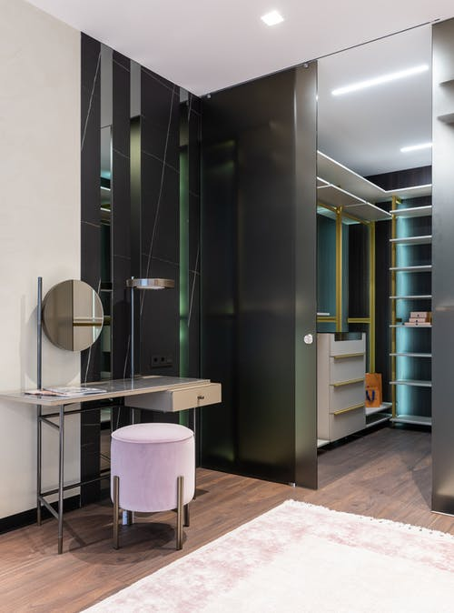 Interior of contemporary apartment with spacious dressing area and vanity table with mirror near padded stool