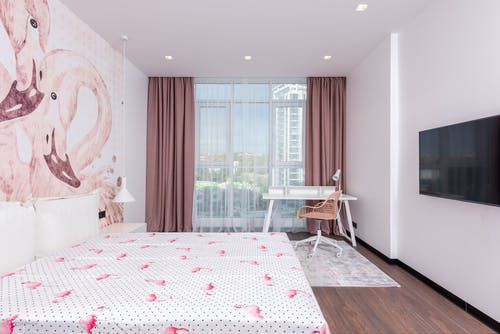 Comfortable room with wide bed under flamingos on walls against TV set and table near huge window