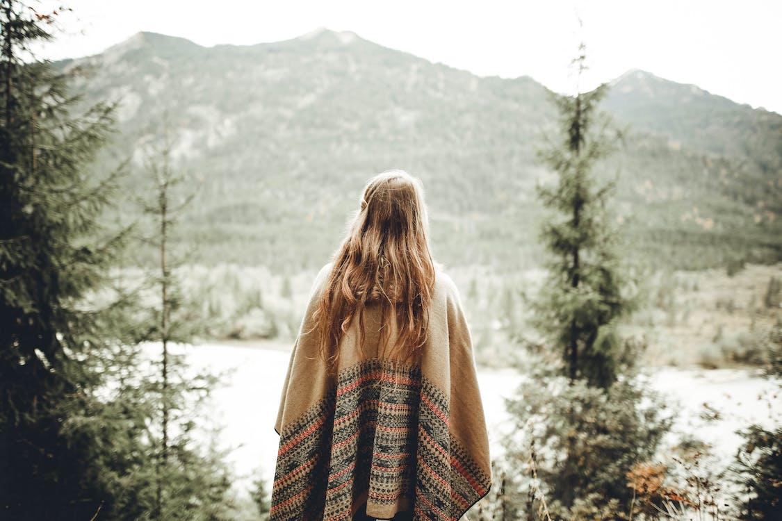 Woman Wearing Brown Poncho Facing Mountain