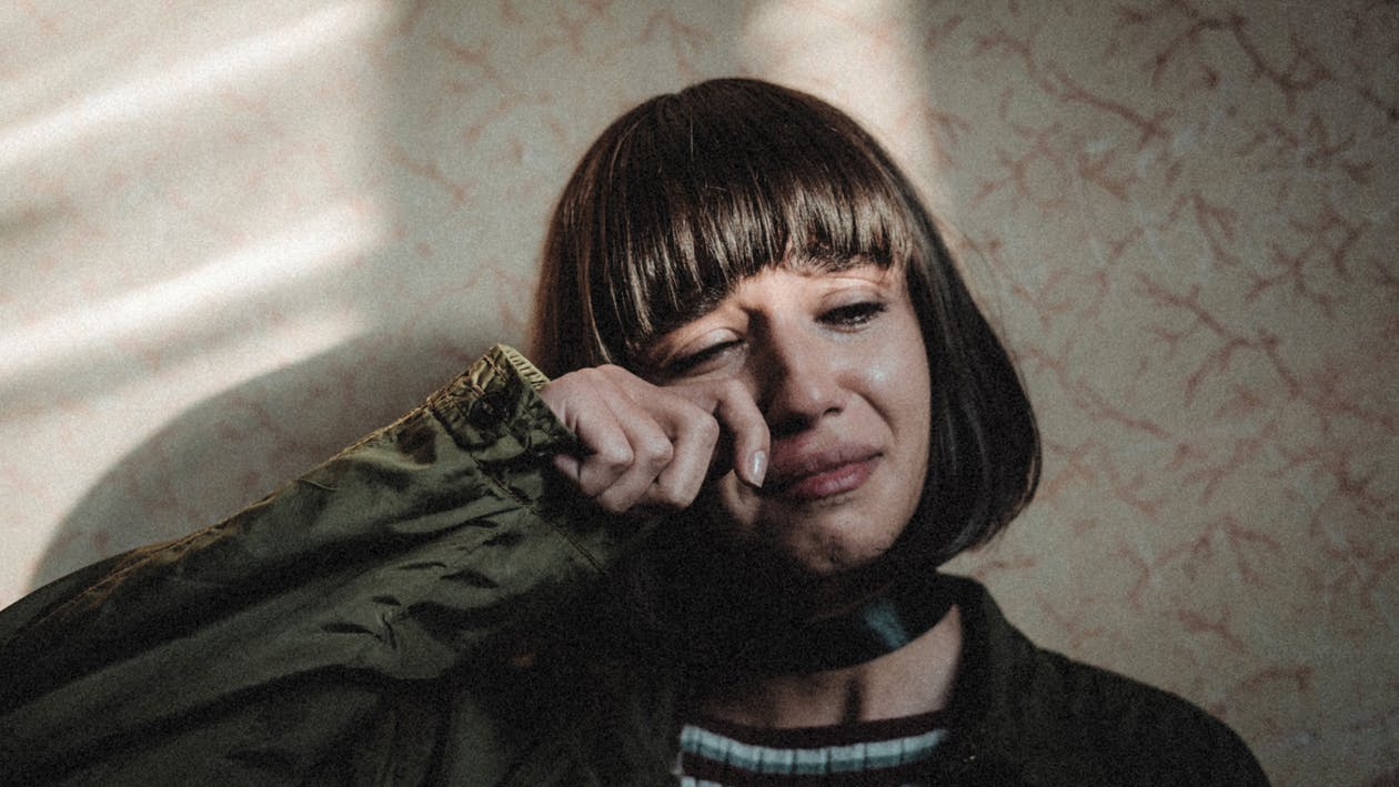 Unhappy female with modern haircut wiping tears while leaning on wall in room