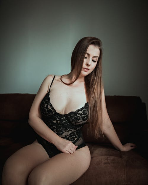 Sensual woman in lingerie on sofa at home