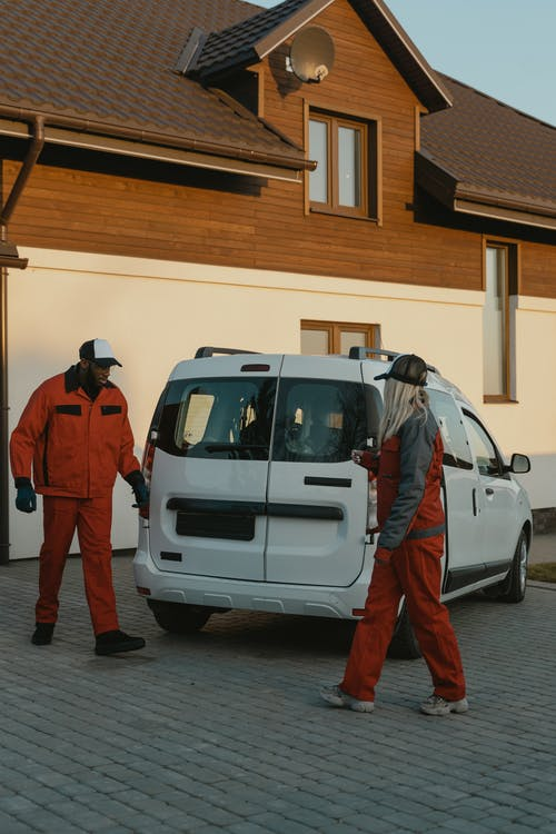 2 Men in Red Jacket Standing Beside White Van