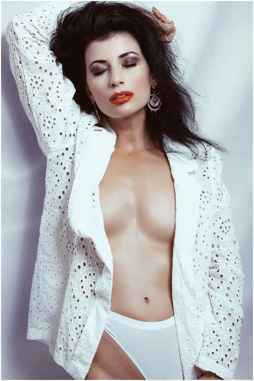Alluring female with bright makeup and dark hair in white lace jacket standing with raised hand and closed eyes against white fabric