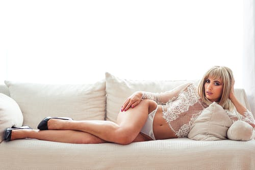 Sensual woman with blond hair in lace underwear and lying on comfortable sofa and looking at camera against white background