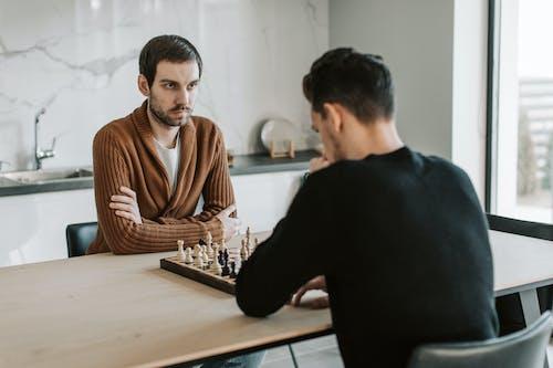 Man in Black Sweater Sitting Beside Woman in Brown Sweater