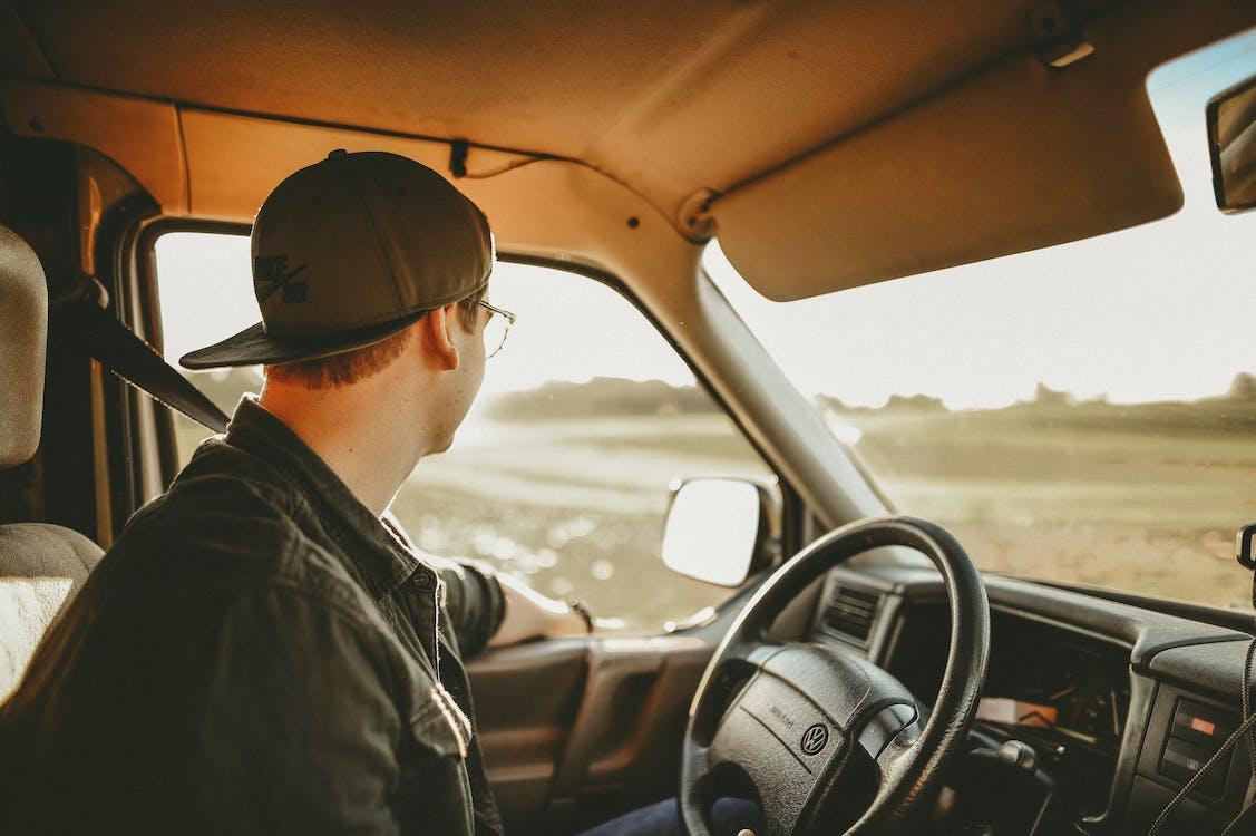 Man Wearing Black Denim Jacket in Driver's Seat