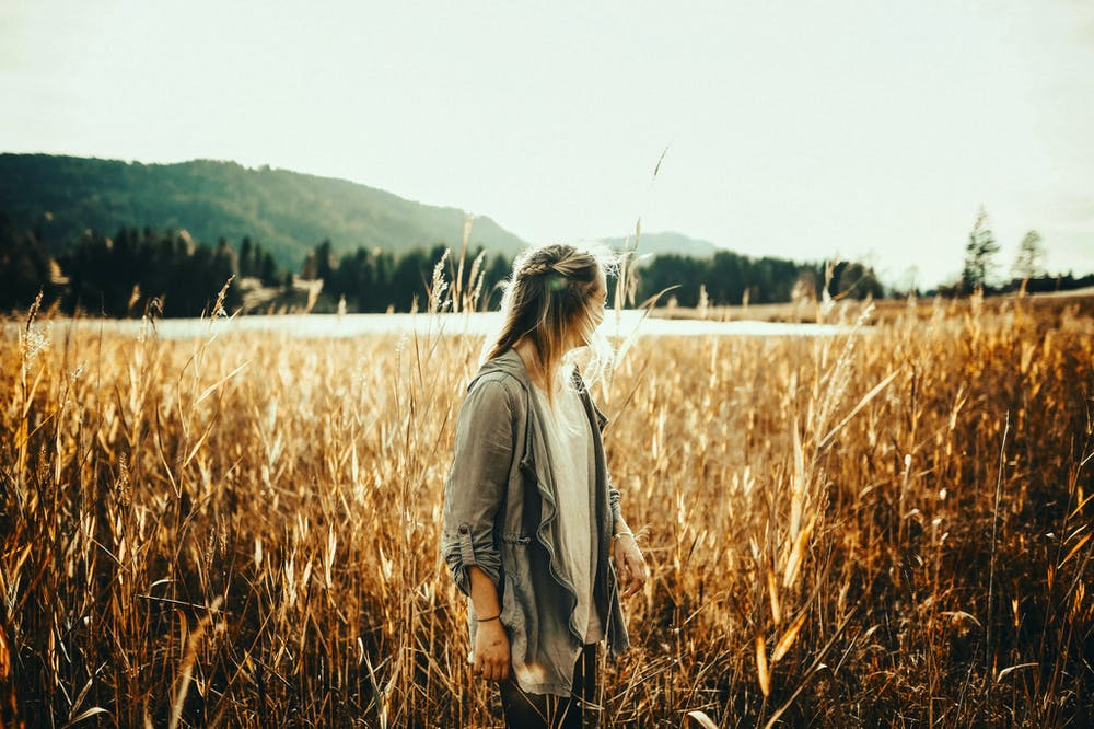 A woman standing in the middle of the field. | Photo: Pexels