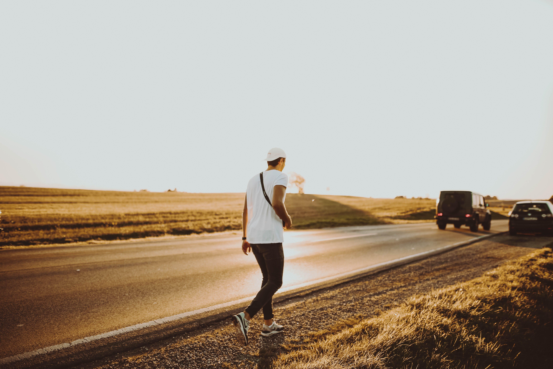 Man Walking Towards Vehicles on Road