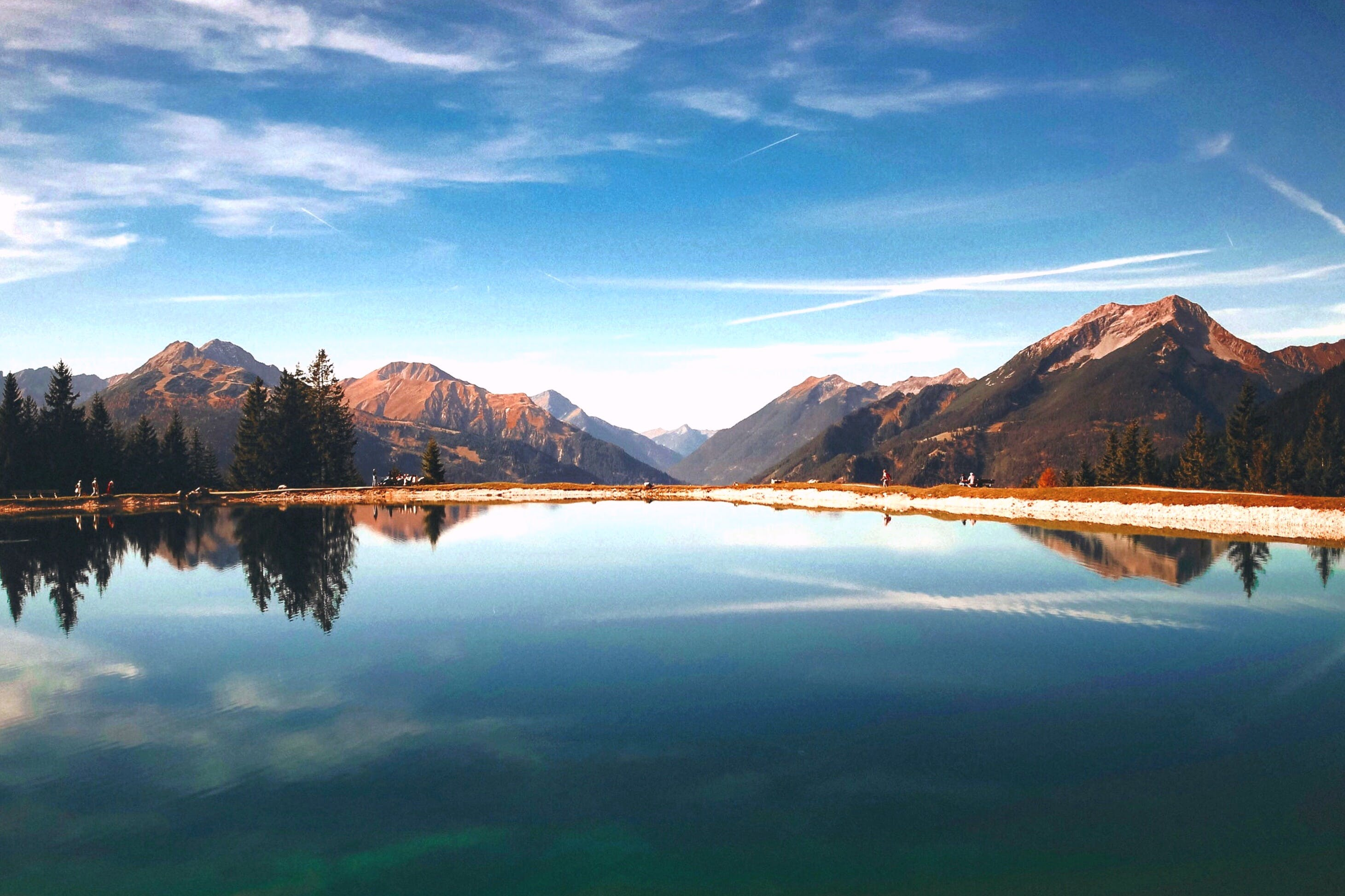 Landscape Photography of Brown Mountains Surrounding Lake