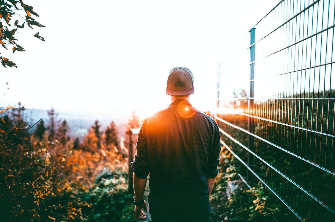 Man Walking Near Gray Steel Fence