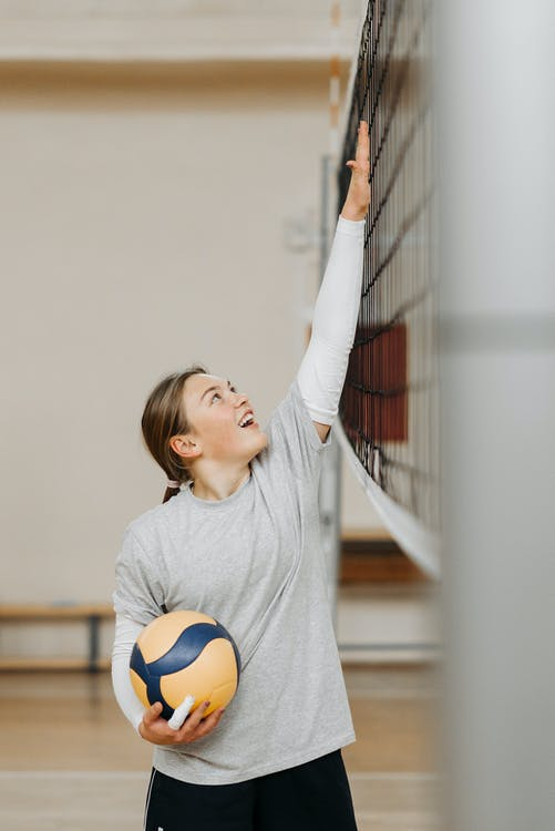 Girl in Gray Crew Neck T-shirt Holding White and Yellow Soccer Ball