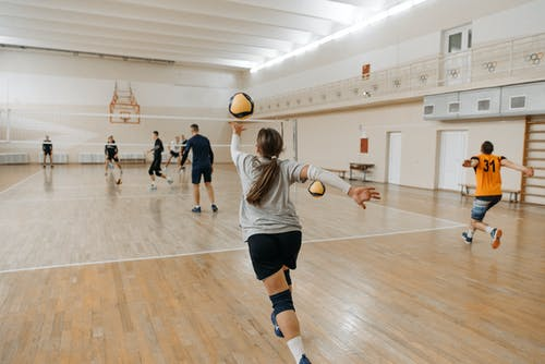 Woman in White and Black Stripe Shirt Playing Basketball