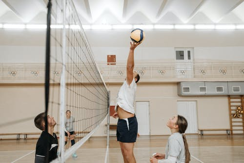 A Man Jumping to Cath the Ball