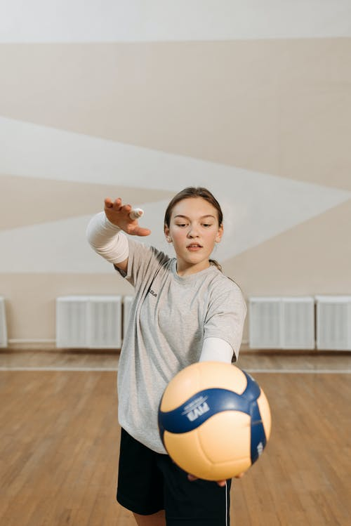 Woman in Gray Shirt Holding Blue and Yellow Ball
