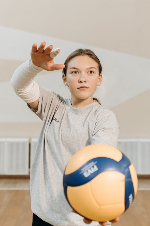 Girl in Gray Long Sleeve Shirt Holding Yellow and Blue Volleyball